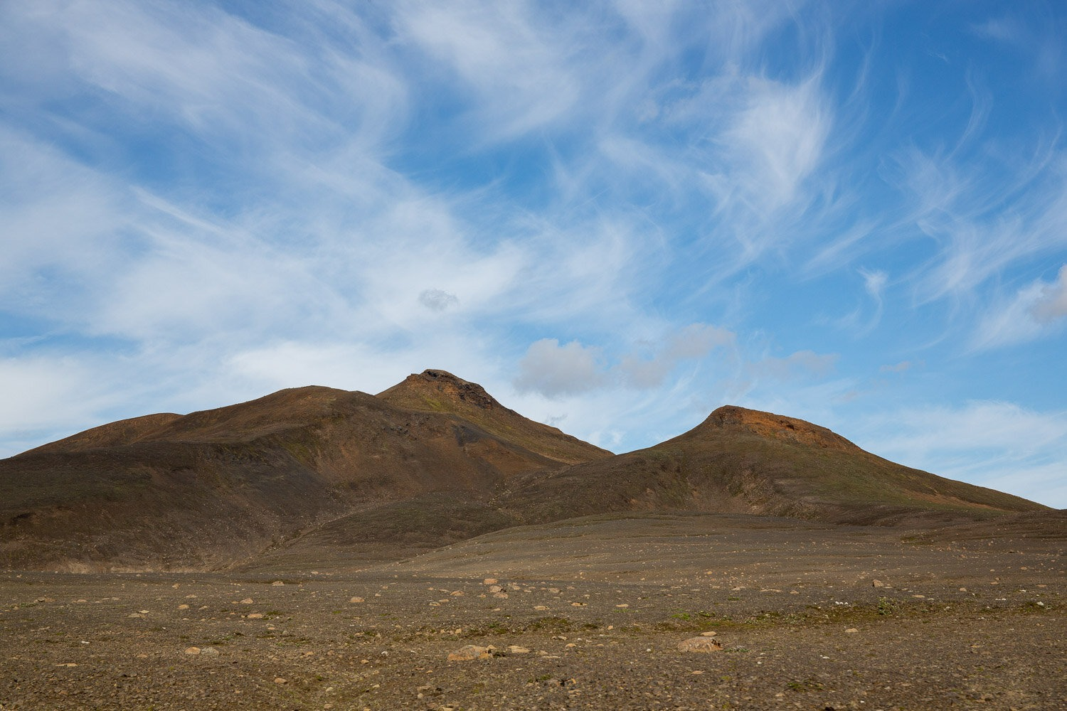 A red volcano with blue sky and cllouds behind