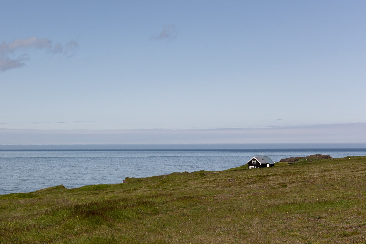 A small house on a cliff top in Iceland with water behind