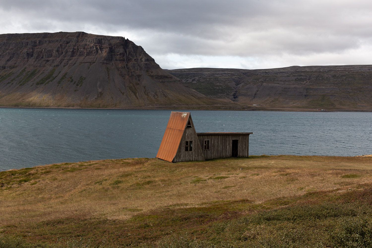 barn with fjord and mountains behind