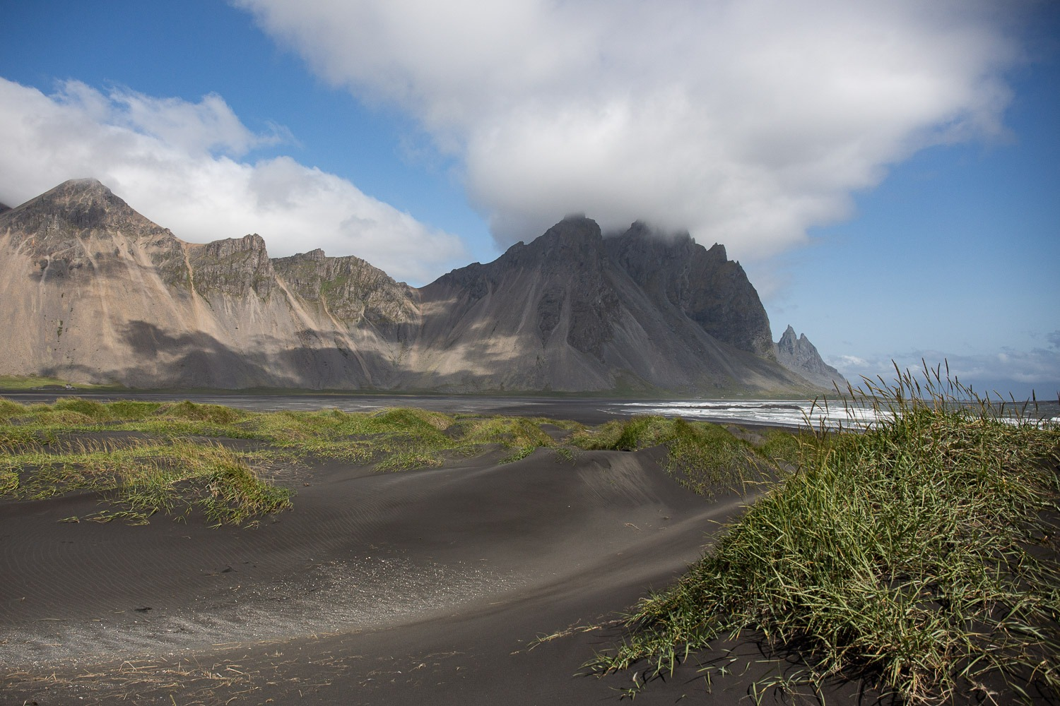 black sand beach with mountains behind