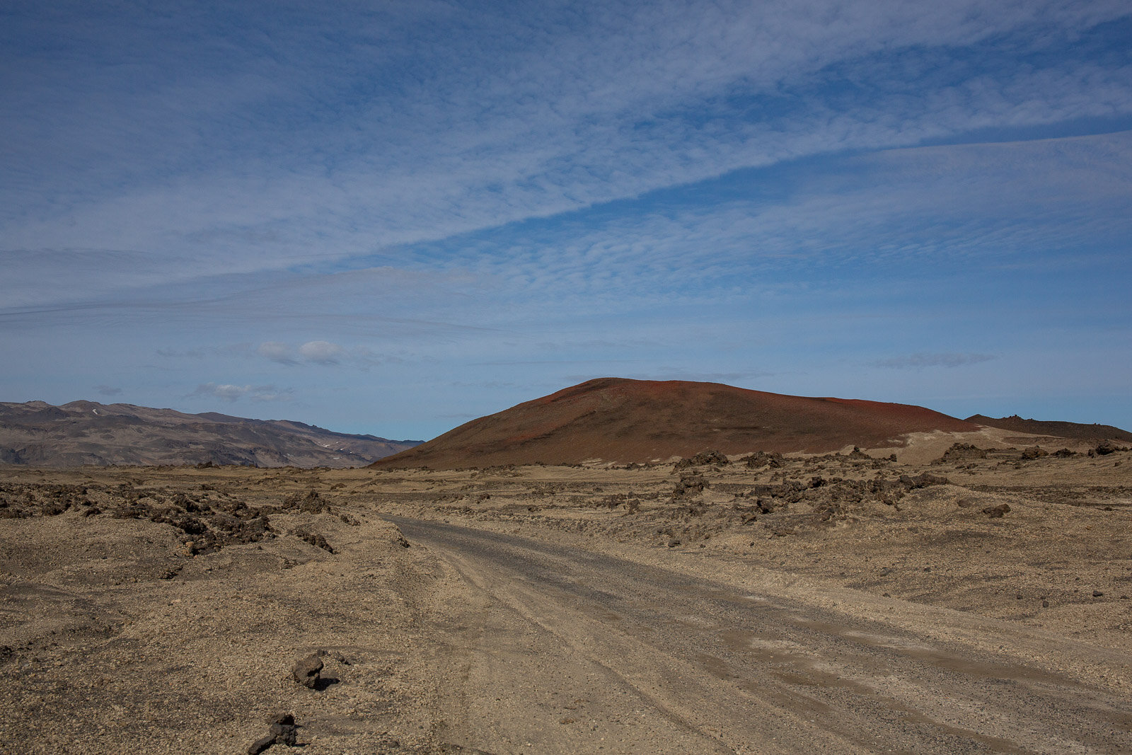 road across a lava field with blue sky