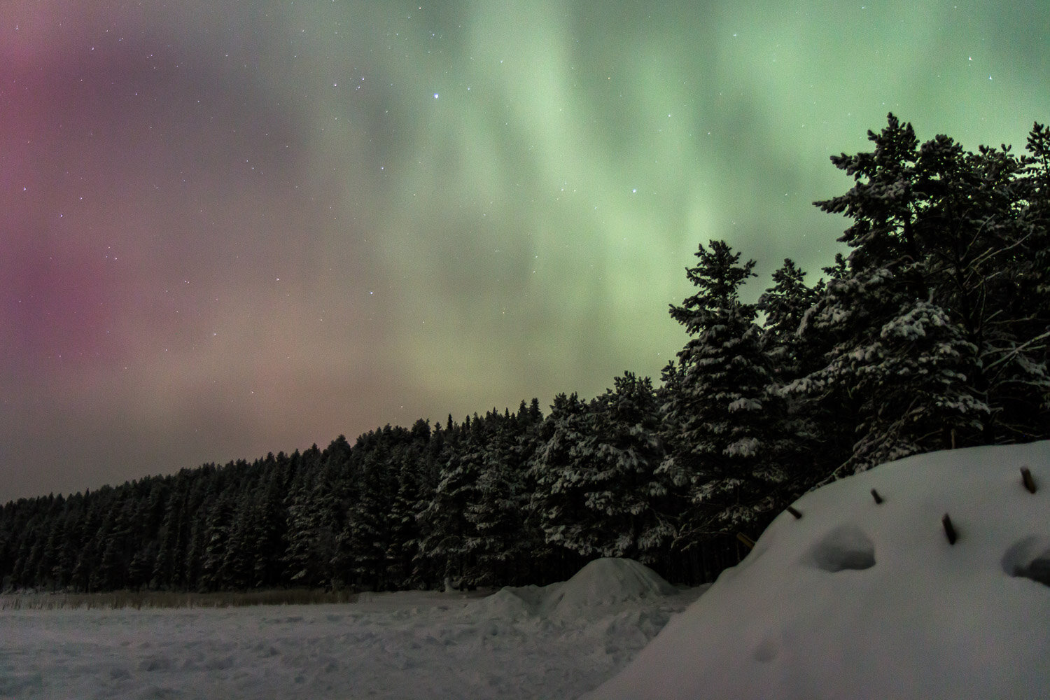 northern lights over a snow hit in Finland