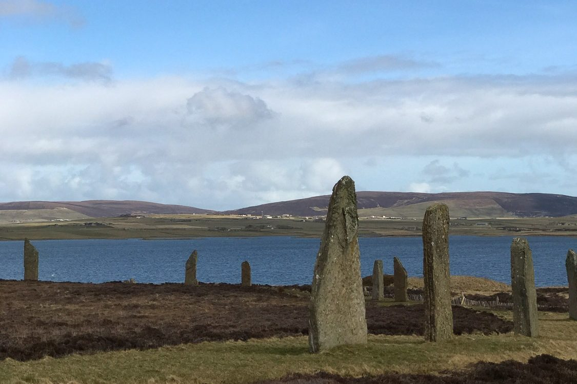 standing stones with blue sky and water