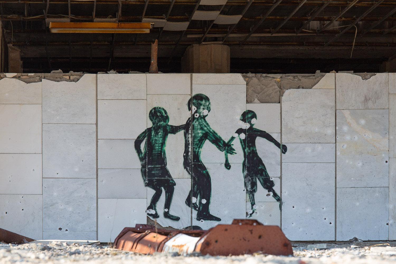 Street art of three figures jumping over a barrel