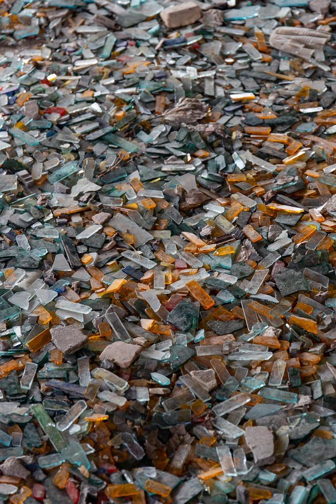 Broken shards of coloured glas son a dusty floor