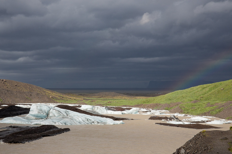 glacial lagoon with a rainbow against a dark sky