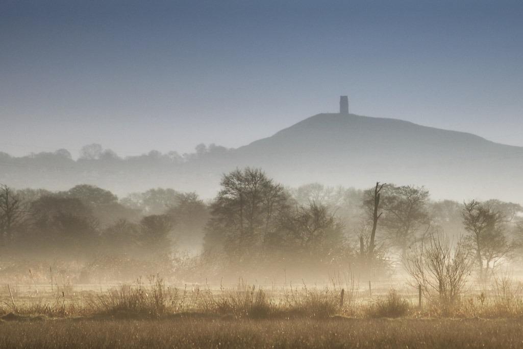 glastonbury tor across fields in mist