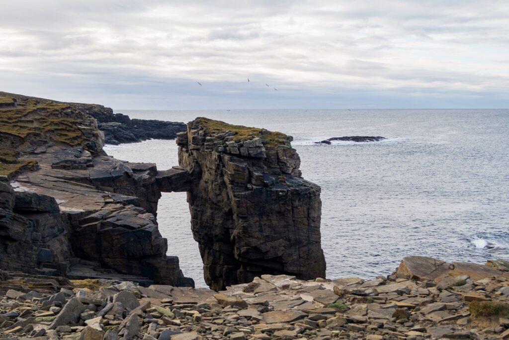 sea stack with small bridge