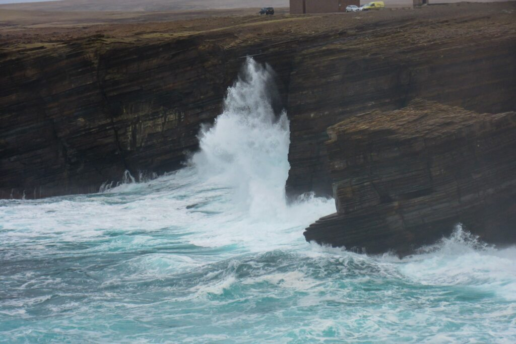 waves breaking up a cliff