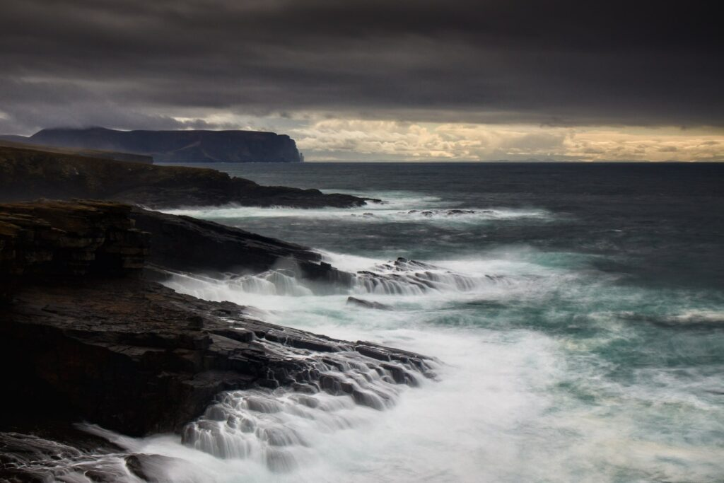 Rough seas against rocks with light in sky