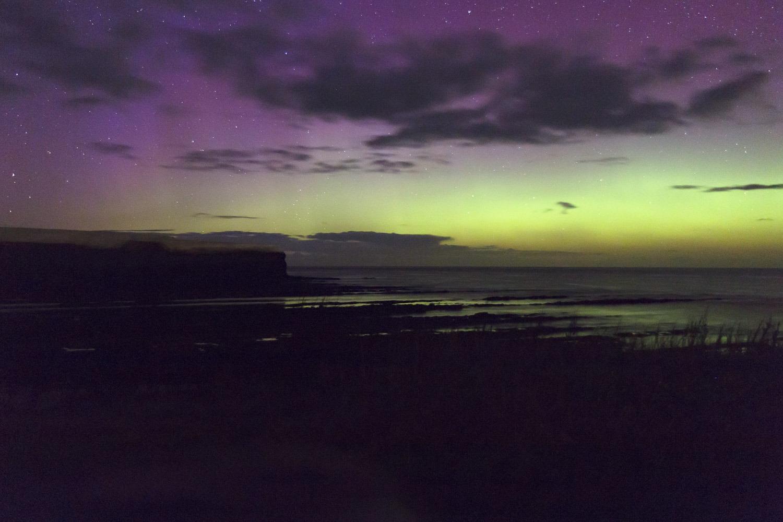 Green northern lights over sea