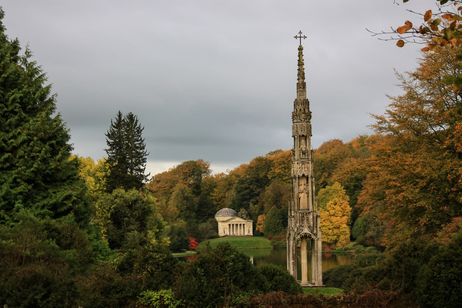 An ancient cross with building behind at Stourhead gardens