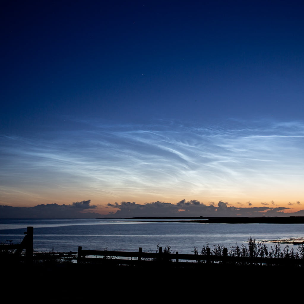 dark sky with shimmering noctilucent clouds over a bay