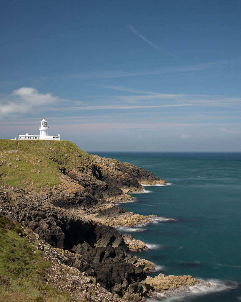 lighthouse in a rocky headland with blue sea and sky