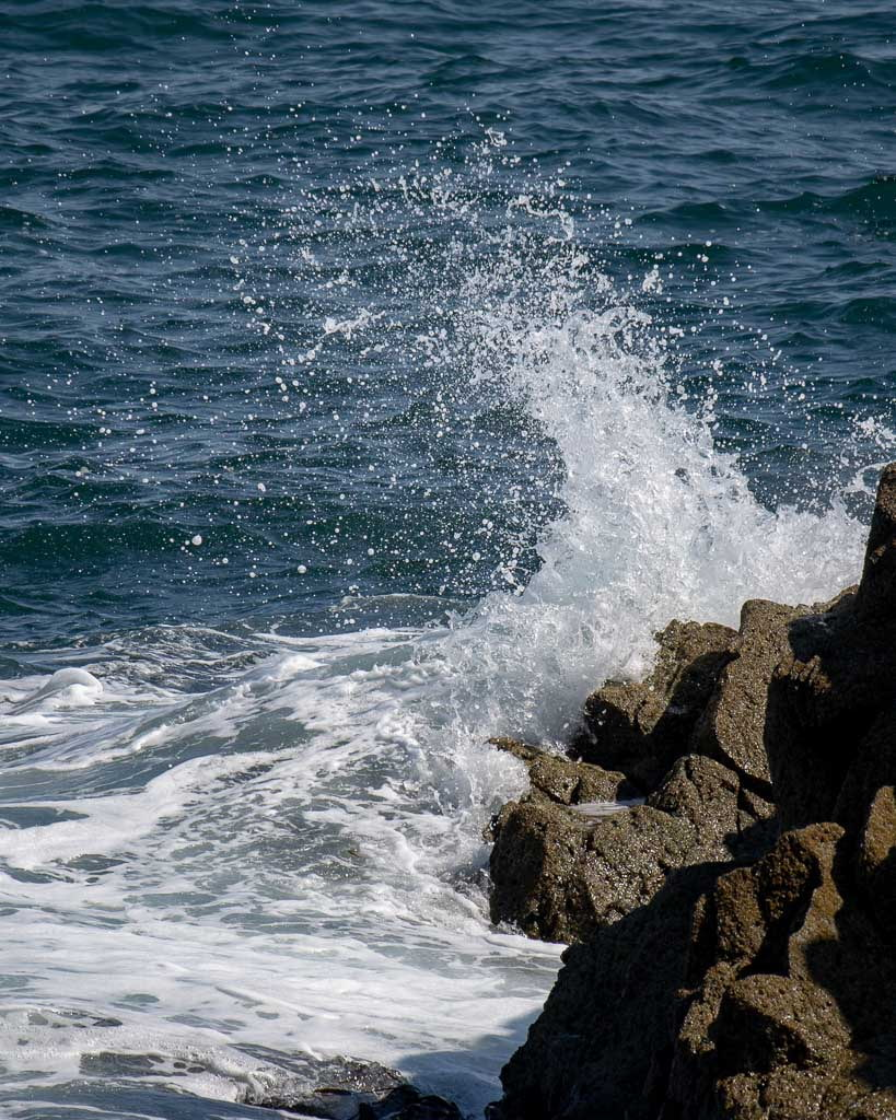 Wave breaking over a brown rock